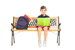 Schoolboy sitting on a wooden bench and reading a book Royalty Free Stock Images