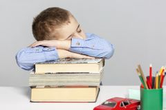 Schoolboy  sleeps on the books for doing homework. Close-up. Gray background stock photos