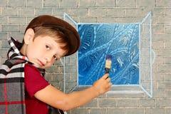 Schoolboy. Small artist, boy draws on the window frostwork Stock Photography