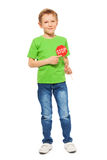 Schoolboy with small Stop sign in his hand. Full-length portrait of seven years old boy in green tee and denim, pointing to a small red Stop sign icon, isolated royalty free stock photos