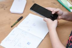 Schoolboy with smartphone doing homework at home.  Royalty Free Stock Photos
