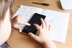 Schoolboy with smartphone doing homework at home.  Royalty Free Stock Photography