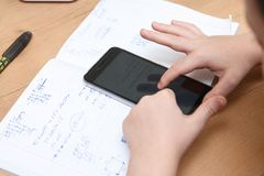Schoolboy with smartphone doing homework at home.  Stock Photo