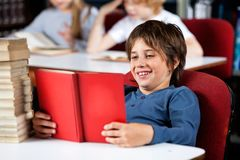 Schoolboy Smiling While Reading Book At Table In Royalty Free Stock Images