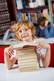 Schoolboy Smiling While Sitting With Stack Of Royalty Free Stock Images