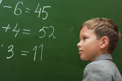 The schoolboy solves examples. The schoolboy at a lesson of mathematics at a school board Royalty Free Stock Image