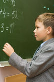 The schoolboy solves examples. The schoolboy at a lesson of mathematics at a school board Stock Images
