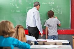 Schoolboy Solving Mathematics. Rear view of schoolboy solving mathematics on board with teacher in classroom Royalty Free Stock Photography