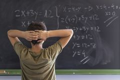 Schoolboy solving a problem on a blackboard. royalty free stock photography