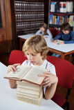 Schoolboy With Stacked Books Reading In Library Stock Images