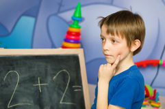Schoolboy standing by the blackboard. Being deep in thought Royalty Free Stock Photos