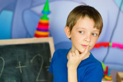 Schoolboy standing by the blackboard. Being deep in thought Stock Image
