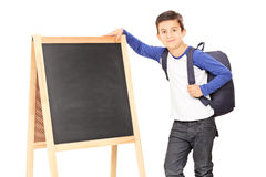 Schoolboy standing by a blackboard Stock Images