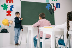 Schoolboy standing at chalkboard and looking at classmates sitting stock image