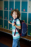 The schoolboy standing near lockers in school hallway. Elementary school student standing near lockers in school hallway. Behind kid's school backpack royalty free stock image