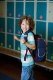 The schoolboy standing near lockers in school hallway. Royalty Free Stock Image
