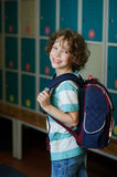 The schoolboy standing near lockers in school hallway. Elementary school student standing near lockers in school hallway. Behind kid's school backpack. The boy royalty free stock photos