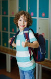 The schoolboy standing near lockers in school hallway. Elementary school student standing near lockers in school hallway. Behind kid's school backpack. The boy stock photography