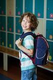 The schoolboy standing near lockers in school hallway. Elementary school student standing near lockers in school hallway. Behind kid's school backpack. The boy royalty free stock images