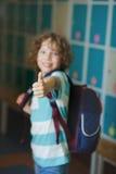 The schoolboy standing near lockers in school hallway. Stock Photography