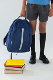Schoolboy standing with school bag and books on white background. Low-section of schoolboy standing with school bag and books on white background Royalty Free Stock Photography