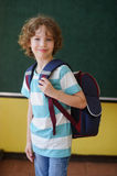 The schoolboy stands in the class near a board. Stock Photography