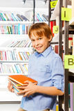 Schoolboy stands and holds books in library Stock Photo