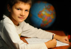 The schoolboy studies. The schoolboy does a homework behind a table Stock Photography