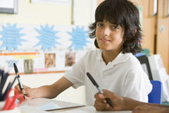 A schoolboy studying in class Stock Images