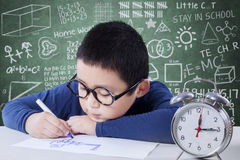 Schoolboy studying with a clock on the table Stock Image