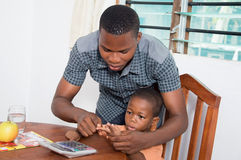 Schoolboy studying with his home teacher. The home teacher of this child learns his to count Royalty Free Stock Photography