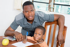 Schoolboy studying with his home teacher. The child with his teacher watch the camera for a shoot Royalty Free Stock Photos