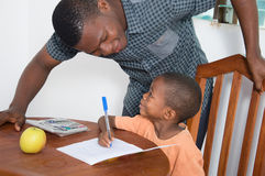 Schoolboy studying with his home teacher. The teacher explains something to the schoolboy looking at his face Royalty Free Stock Photo