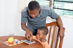 Schoolboy studying with his teacher at home. Child's teacher shows him the numbers on the calculator Stock Image