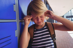 Schoolboy suffering from headache while standing by lockers. In corridor at school Stock Images