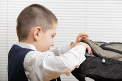 Schoolboy taking book from backpack Royalty Free Stock Image