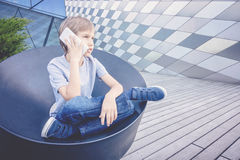 Schoolboy talking on the phone in the city Stock Photography