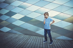 Schoolboy talking on the phone in the city Royalty Free Stock Images