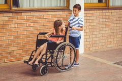 Schoolboy talking to a girl on wheelchair Stock Images