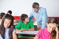 Schoolboy And Teacher Looking At Each Other During Stock Images