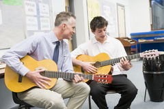 Schoolboy and teacher playing guitar stock photography