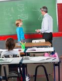 Schoolboy And Teacher Standing By Board In Stock Images