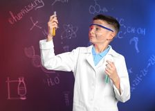 Schoolboy with test tubes against blackboard with chemistry formulas. Schoolboy with test tubes against blackboard with written chemistry formulas stock images