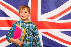 Schoolboy with textbooks against English flag. Smiling schoolboy with textbooks in his hand standing against English flag Stock Photo