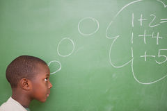 Schoolboy thinking about additions Royalty Free Stock Images