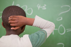 Schoolboy thinking with his hand on his head. In front of a blackboard Stock Photos