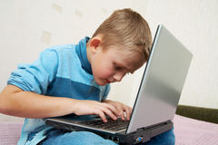 Schoolboy to laptop Royalty Free Stock Photography