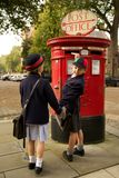 Schoolboy turning while posting letter with sister Stock Photo