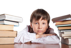 The schoolboy between two heaps of books Royalty Free Stock Image