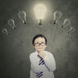 Schoolboy under bright lightbulb Stock Images